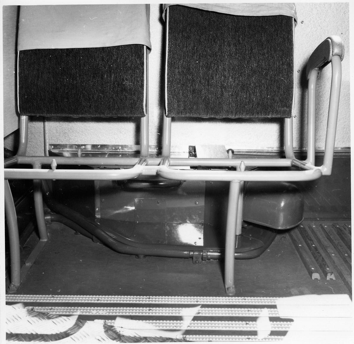 Interiör från en buss. Sittplatser utan sitsar.