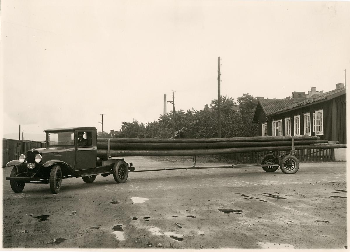 Chevrolet lastbil med vändskiva och släpkärra för långgods fraktar telefonstolpar.