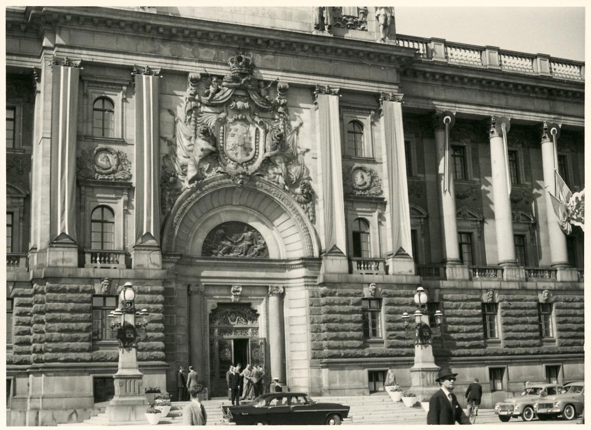 Fordon och människor framför entréportalen till Riksdagshuset i Stockholm.