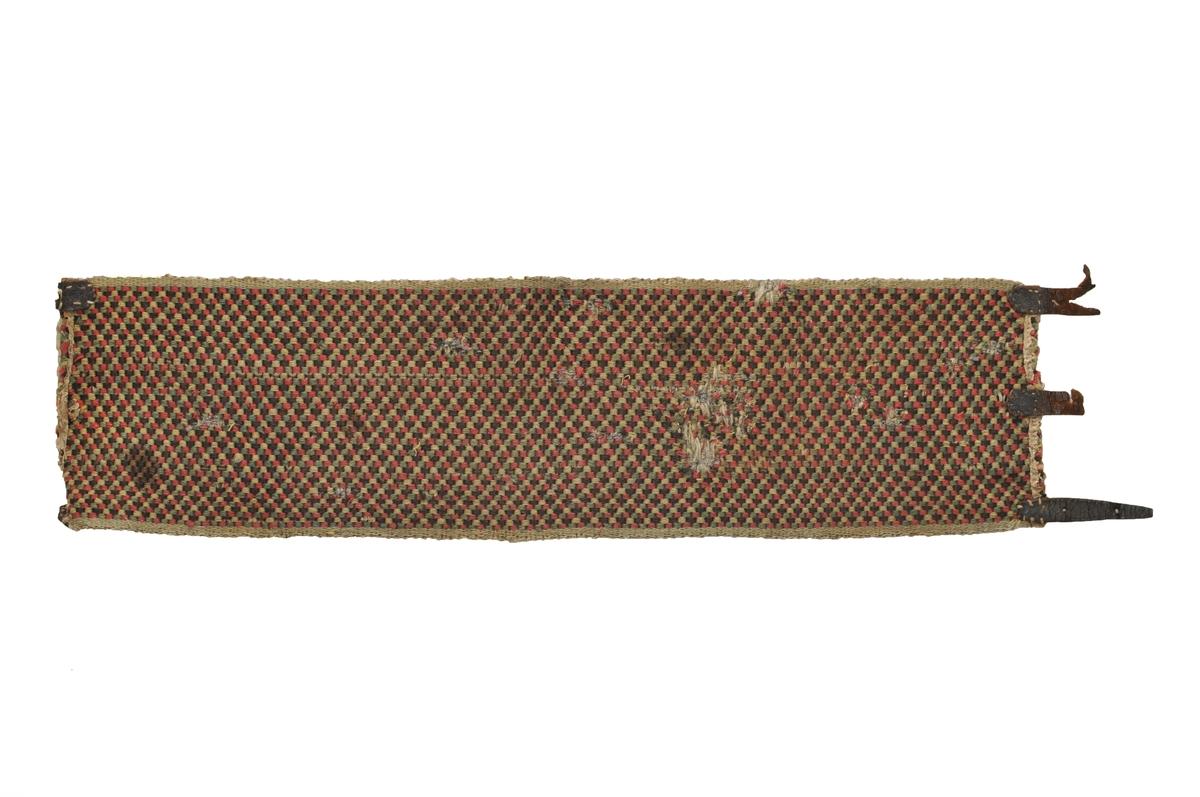Belte vevd i brikkevev i brun, grønt og gult ullgarn. Belte har diagonalt mønster.  I ytterkantane langsgåande striper. Fora i endane med lin. (slitt)  I eine sida tre lærreimar for å halda belte i saman med, den andre sida har to lærlappar med merke etter at det har vore spenner der. Den midterste manglar.