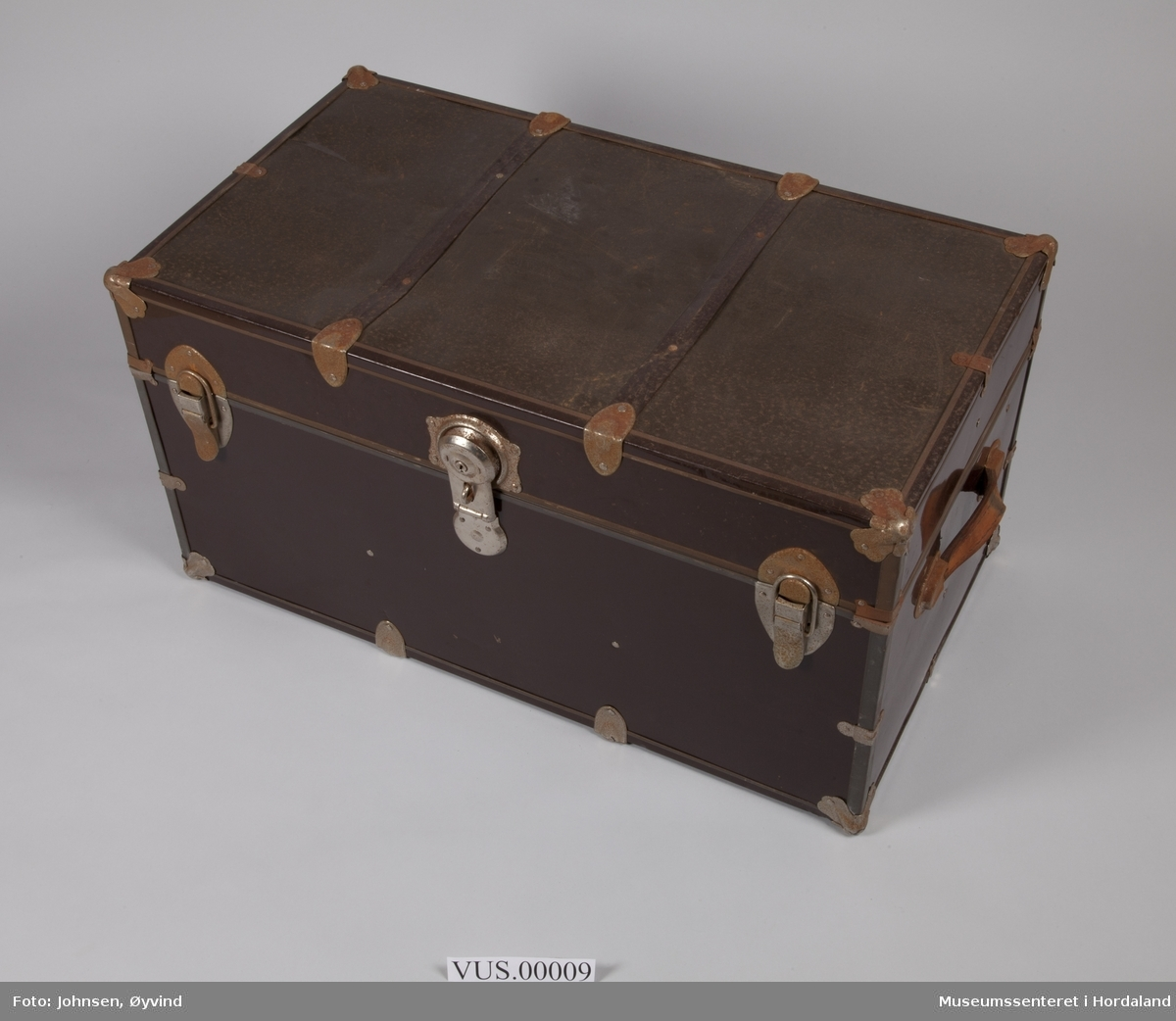 Brun, dyp koffert med lås og to hengsler. To bærehåndtak, metallforsterkninger på hjørner. Trukket med blått- og hvitmønstret papir innvendig. Er påklistret/påhengt tre etiketter med tekst.