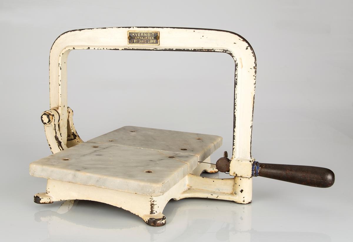 Osteskjærer til butikkbruk. Støpejern med marmorplater. Platene er kvadratiske med en liten åpning mellom, og er skrudd fast til en liten sokkel med fire ben. På løftearmen er det montert en tynn ståltråd. Denne fungerer som skjærestreng og deler osten ved å klemme ståltråden ned mellom de to platene.