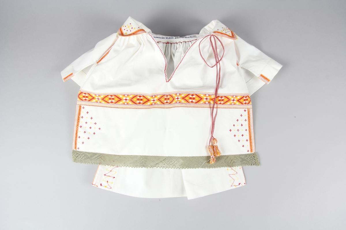 Halskläde till Orsadräkten. Av fem delar bomullstyg. Fram och bakstycke, axellappar och nedvikt krage. Samtliga stycken rynkade mot halsen. Tätt broderad längs med kanter och mitt över. Broderiet är gjort med sytråd i gult, orange, röd och vitt. längs kragens kant är små nuggor sydda till en spets. Halsklädet stängs med ett vävt band med toffsar av sytråd. I nederkanten av framstycket är en knypplad spets fastsydd.