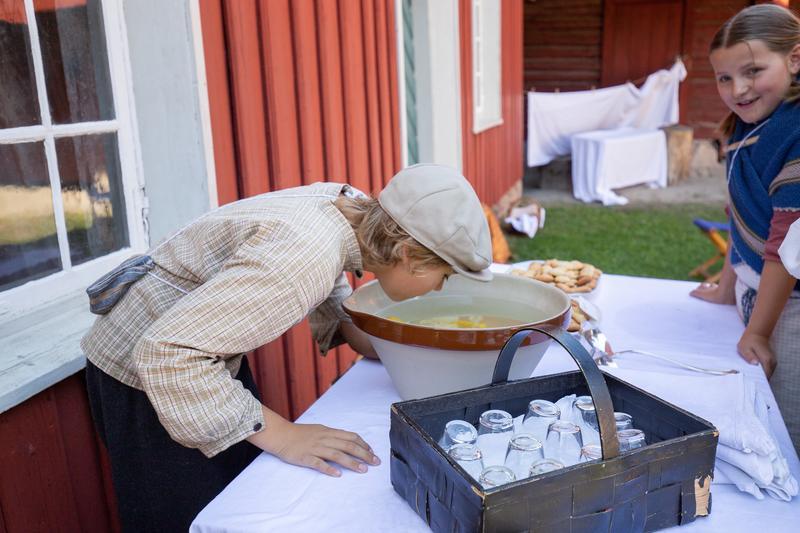 Barn på Historisk ferieskole Norsk Folkemuseum lager limonade.