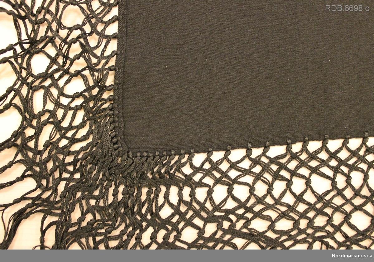 Svart ulltørkle vevd i 2-skaft lerret med frynser. Jare på to sider og smal fald på de to andre. Frynsene er kytt fast til kanten av stoffet og tvunnet sammen i et spesielt mønster.