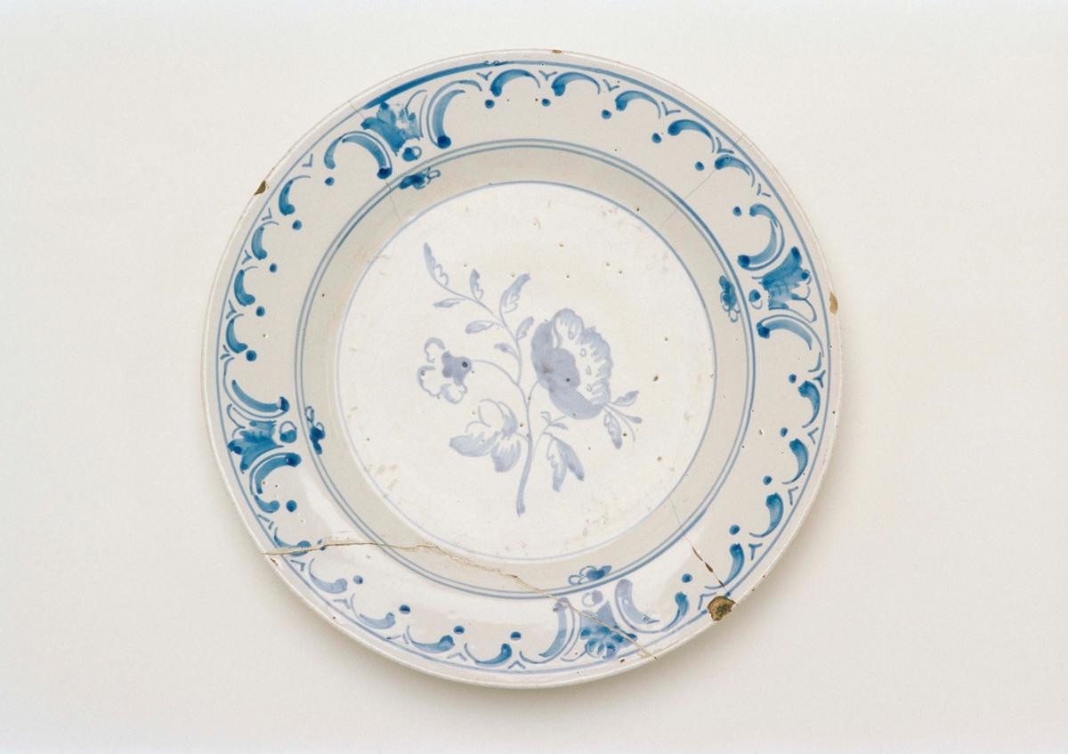 """Flat tallrik av fajans, vit glasyr med blå blomdekor på spegeln, på brättet stiliserad bladdekor. Målad signering: """" Rör 9/11 64 9/3 K """" Stämplad """"M""""."""