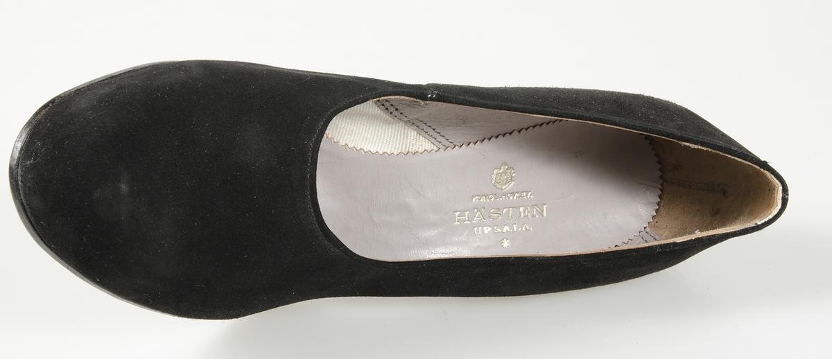 Pumps av svart mocka, klädd klack, lädersula, bakfoder av grått skinn med hälkappa av mocka, framfoder av vit twills, Hästens firmamärke på fyra ställen. Storlek 5. På sulan står skrivet: 26/1 1949, CE har maken.