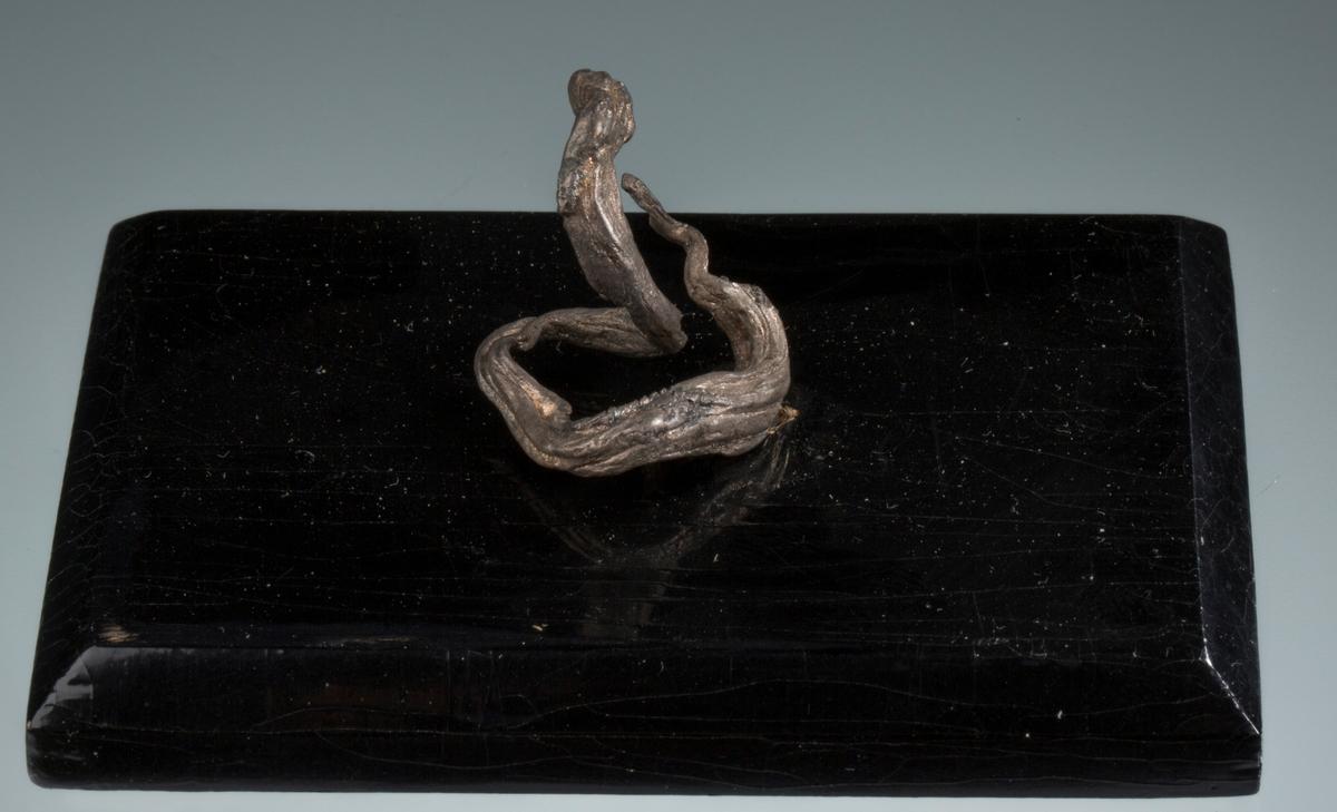 """""""Huggorm"""" på svart plate med påskrift: """"30 gr br, 4 gr n, Huggorm, BVM 3286"""" Vekt: 29,53 g (med sokkel) Størrelse: 2,5 x 2,4 x 2 cm"""