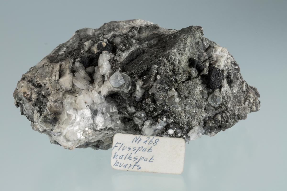 Vannklar krystall, med kalsitt, kullblende, kvarts, (sølv?) Etikett:  Nr 268 Flusspat kalkspat kvarts Vekt 406,03 g Størrelse: 11 x 8 x 4,5 cm