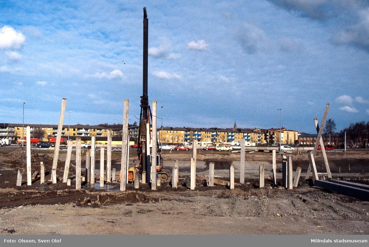 Vägbygge i Åbro, Mölndal, i april 1998. Många pålar slås ner när Åbromotet byggs om. I bakgrunden ses bostadsbebyggelse i Åbyområdet. D 29:19.