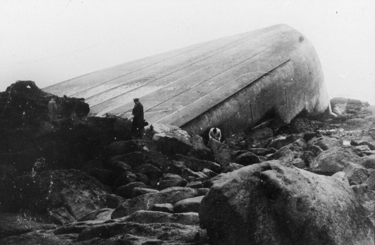 Kvelvet baug fra et stort fartøy i fjæresteinen. Fem mann undersøker vraket.