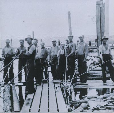 Gammelt foto av lensearbeidere med fløterhaker som poserer for foto ute på lenseanlegget i elva.