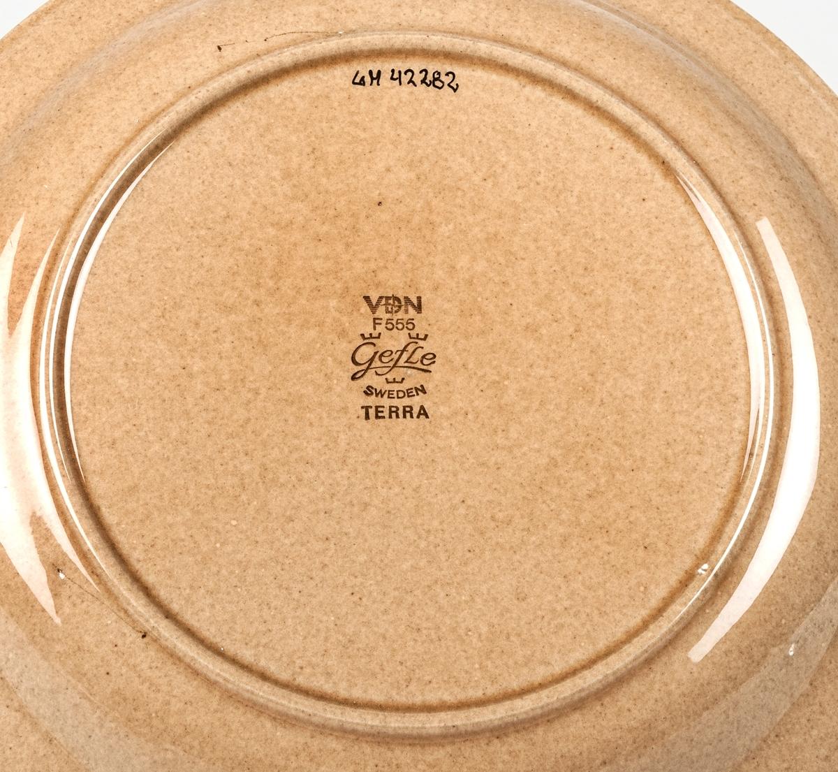 Tallrik, flat tillhörande servisen Terra, ljusbrun bottenglasyr med två mörkare band i brunt samt en reliefdekor ytterst på brättet. Design av Berit Ternell.