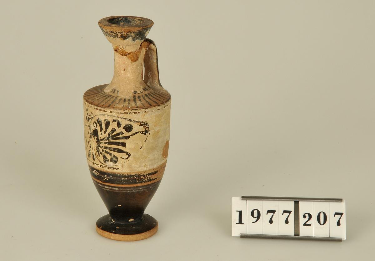 """Flaska av keramik och ett öra. Svartfigurig dekor och en påklistrad etikett med texten """"Acropolis""""."""