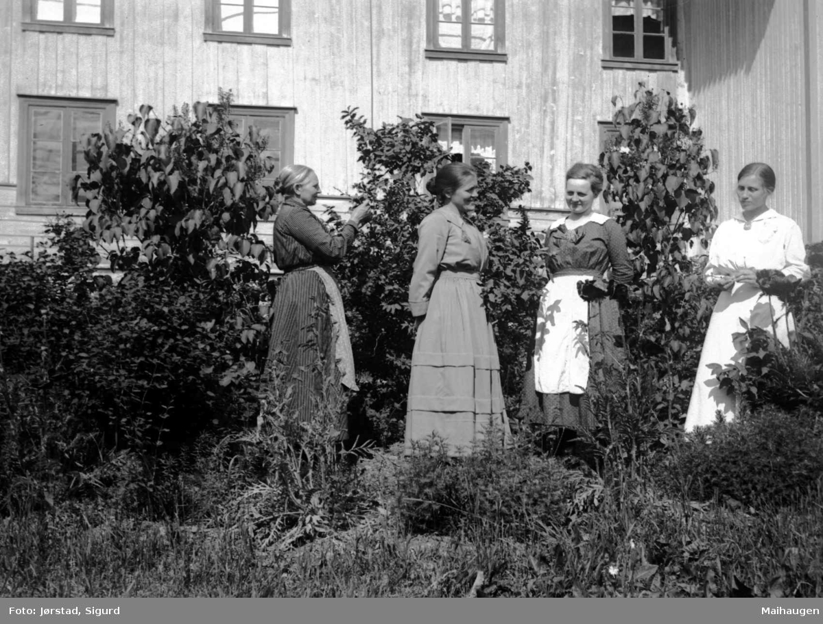 Fire kvinner i en hage utenfor hovedbygningen på Søre Jørstad, Fåberg.
