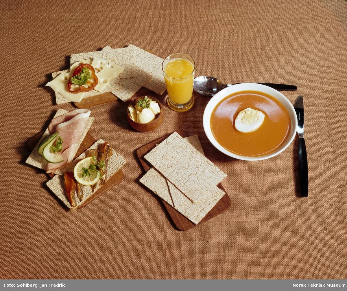 Bildet reklamerer for flatbrød av merket Korni. Et bord er dekket med tomatsuppe og spekemat med flatbrød til. Et glass med appelsinjuice står sammen med maten.