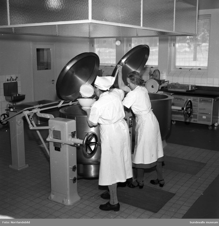 Två kvinnor jobbar i skolbespisningsköket på den nybyggda Hagaskolan.