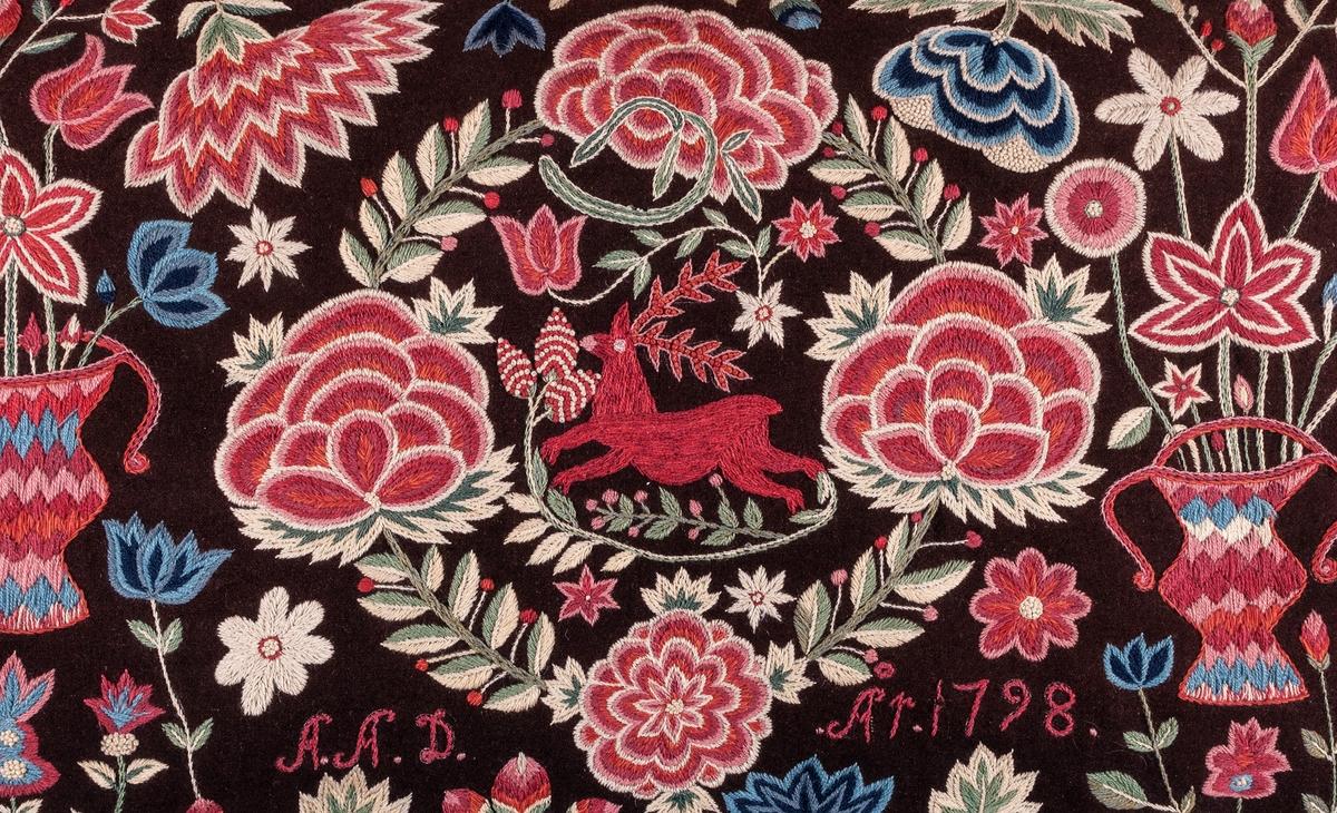 Agedyna, 120 x 56. På brun vadmal broderi i ullgarn i starka färger. Inom en krans en löpande hjort. På sidorna vaser med blommor. Sign. A A D. År 1798. Nedtill insytt M J 1914 D K. Fodrad med röd vadmal, kantad med mångfärgad kavelfrans. Schattérsöm och något stjälksöm. Tillhör samma grupp som de 2 ovanstående. /gröna rummet/ Äldre katalogisering av Elisabeth Thorman (enl. uppgift).