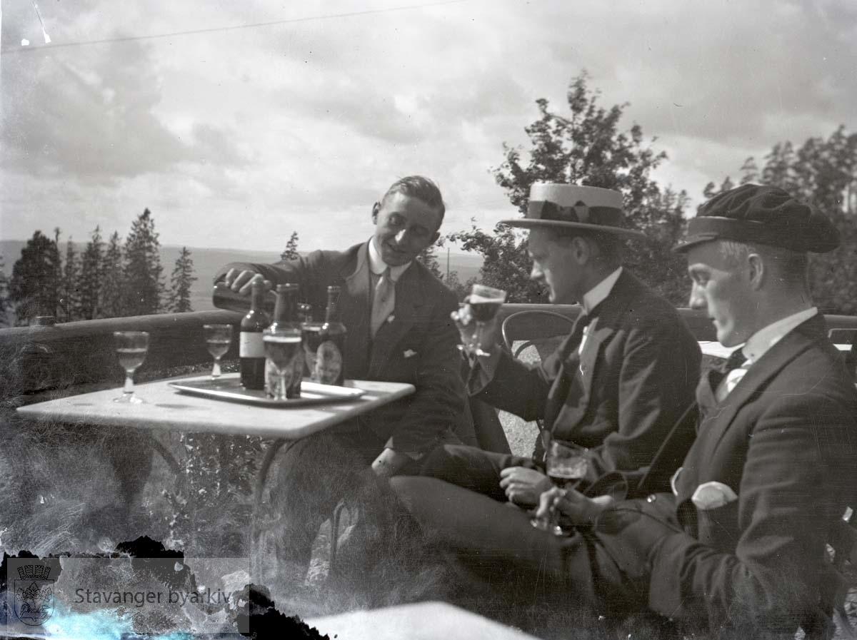 Tre menn drikker øl (?) på veranda.Flasker og glass.