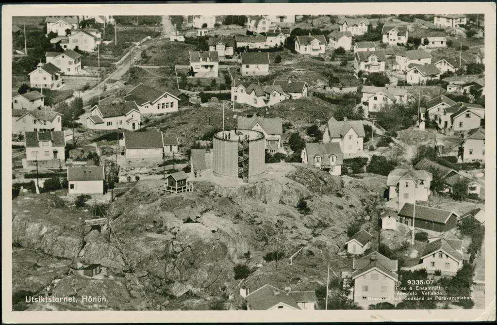 Flygfoto med Hönö utsiktstorn. Utsiktstornet är cyliderformat med en spiraltrappa. Utsiktstornet står på en bergsknalle och flera personer står och blickar ut från både tornet och marken runt om kring. Runt om syns bebyggelse.