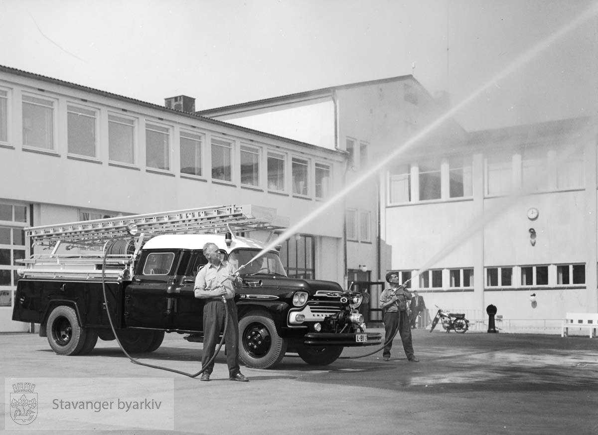 Brannbil oppstilt utenfor den nye brannstasjonen. A. Rasmussen og A. Fosse bruker brannslangene.
