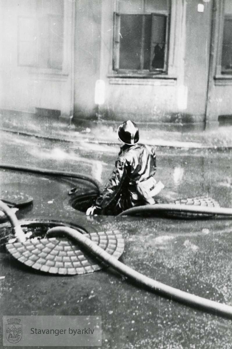 Brannmann ansvarlig fortilkopling av brannslanger. Kumlokk..Grand hotel var en 3 etasjers trebygning reist av skipsreder Søren Berner etter bybrannen i 1860. Privatboligen ble ombygd til hotelldrift i 1887. Etter invasjonen 9. april 1940 rekvirerte den tyske okkupajonsmakten hotellet. 9. mai 1945 ble bygningen antent og totalskadd.