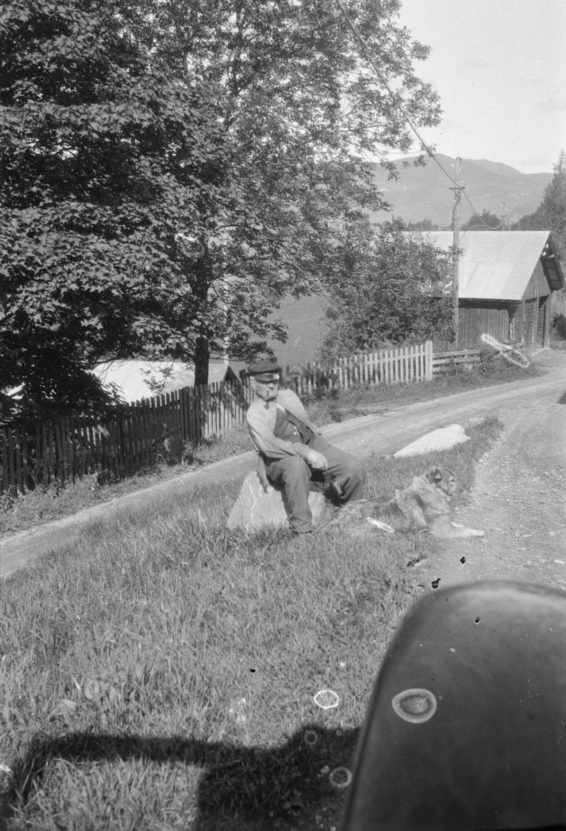 Hans Løbet sittende på en stabbestein utenfor butikken på Linjordet