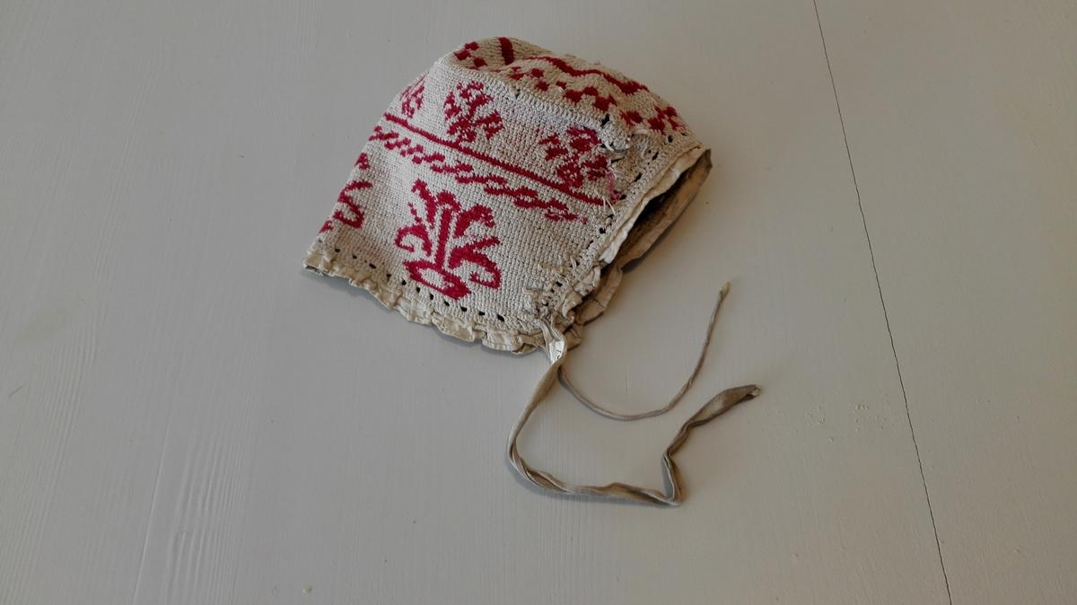 2 barnehuer (16628 - 29)  To heklede barnehuer. Heklet i mönster av hvitt og rödt bomullsgarn. den ene kantet med en heklet blonde, den annen med hvitt töi.  Kjöpt av Unni Stadheim, Vik i Sogn.