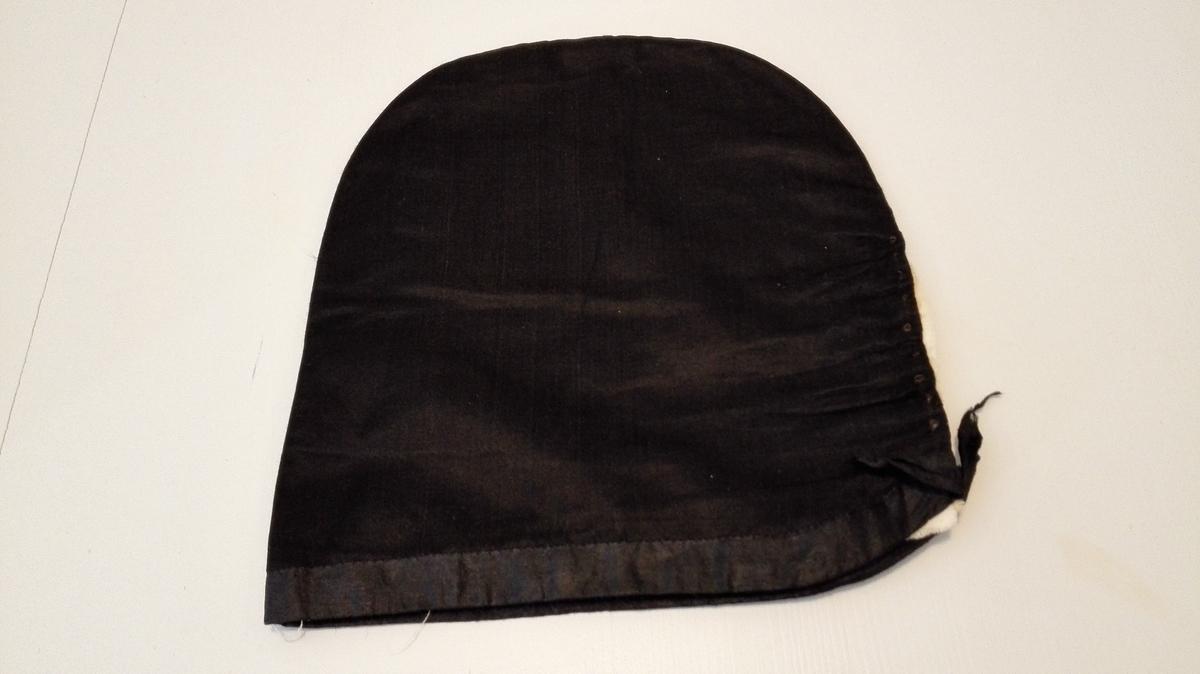 Svarthue: Sjå omtale av svarthue på nr. 6100.   6101 -  Av sort klæde, nedentil kantet med sort mønstret baand og indv. foret med blaat glat tøi.  Til denne hører form av lærred.  Kjøpt paa auktion paa Storaker i Hyllestad ved lensm. A. Faleide.