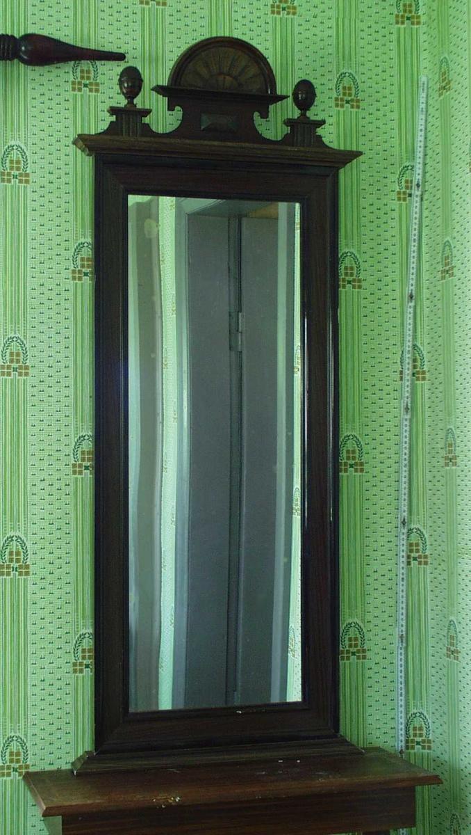 Dekorasjon oppå speilet: To eggformede kuler på fot, på hver side av utskåret blomst.