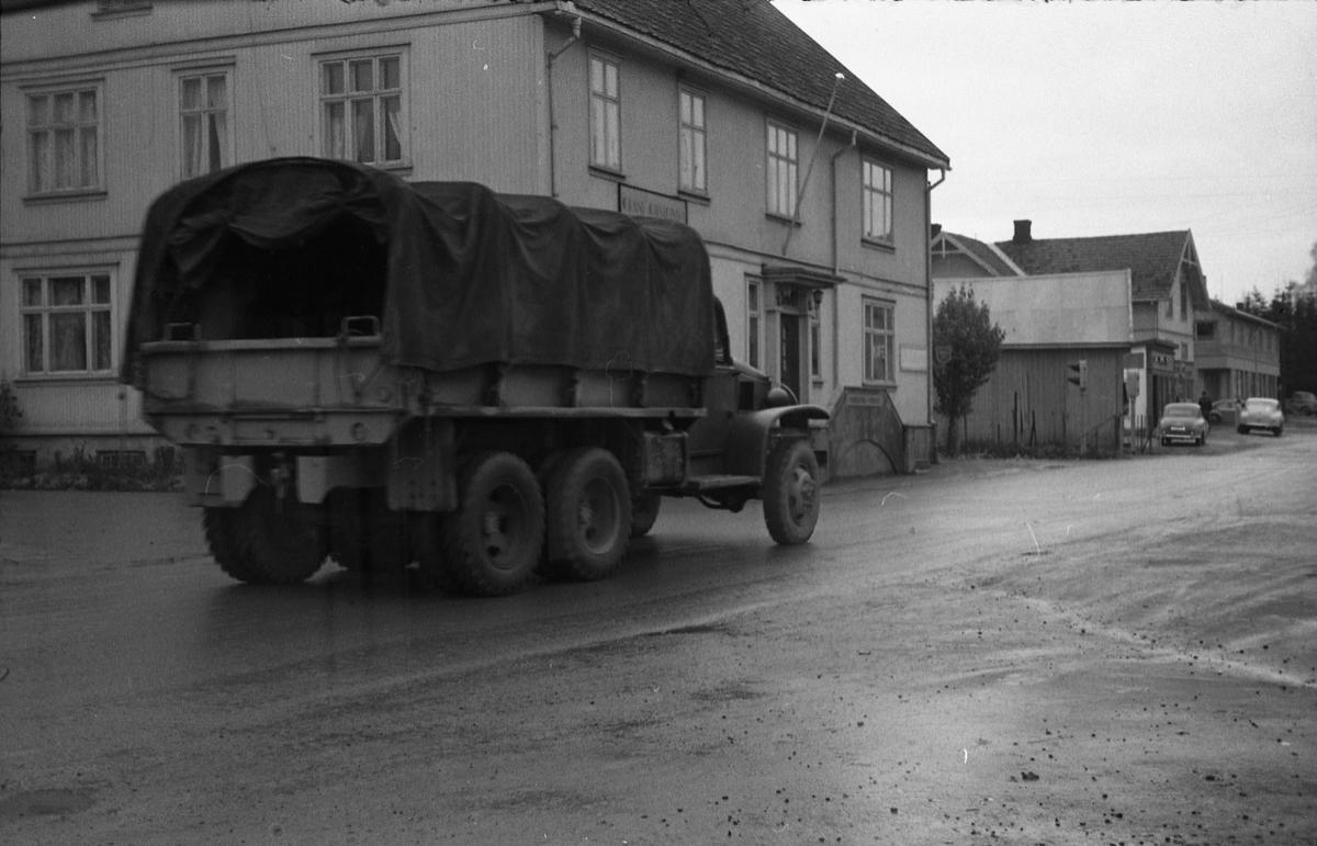 """To gatebilder fra Lena sentrum september/oktober 1957. Det første viser to militære kjøretøy, en jeep og en lastevogn med kapell (ifølge informant en GMC), foran Esso-stasjonen, det andre lastebilen på veg opp Lenagata. Bildene er tatt gjennom vinduet i Lena Foto & Radio i """"Raubua""""."""
