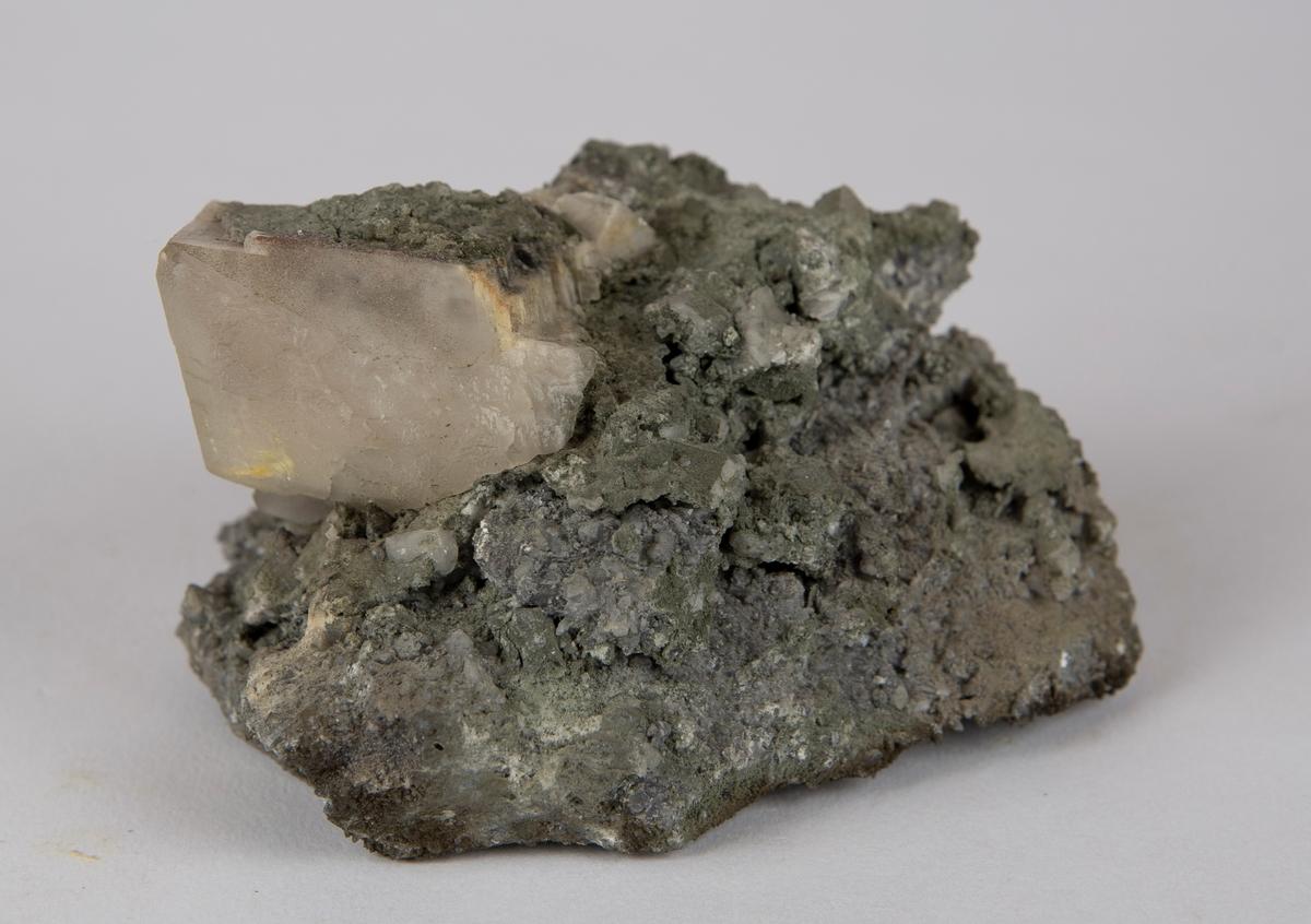 Krystall av kalsitt, omtrent 4 cm x 4 cm x 3 cm, på matriks av kloritt og leirmineraler (?). Gottes Hülfe in der Noth, nordlige gang nr. 1, 300-320 m.