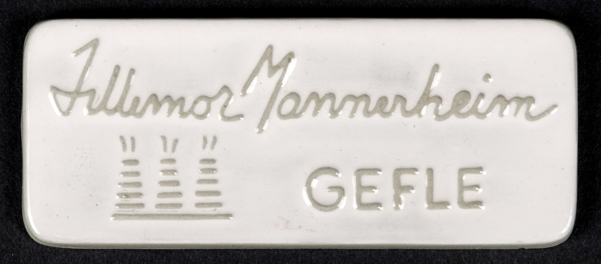 Skylt med stämplad dekor, texten lyder: Lillemor Mannerheim. GEFLE. Samt de tre ugnarna.