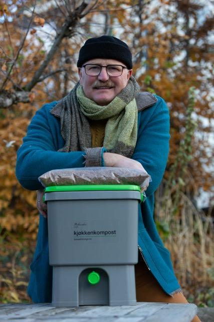 Odd Hauge, iført blå vindjakke, svart strikkelue og skjerf står og lener seg på en komposteringsbeholder i grå plast.