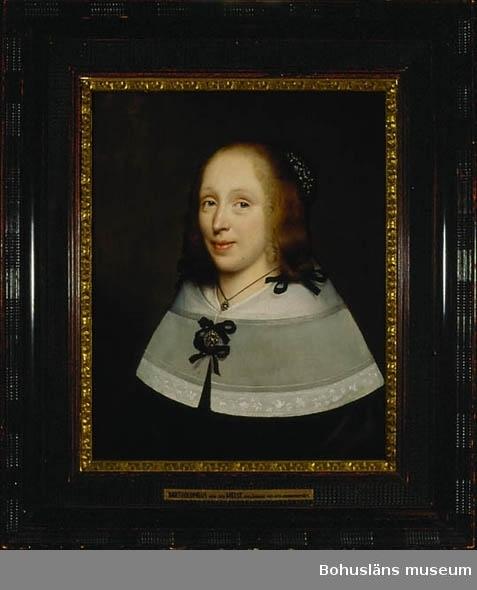Bartholomeus van der Helst. Född i Holland 1613, död 1670. Porträtt av okänd dam. 64,3 x 51,8. Olja på träpannå.  MONTERING/RAMNING Träpannå av ek, med kassetterad baksida. Troligen utfört på 1800-talet med ett system av vinkelställda ekribbor, varav de lodräta är limmade mot träskivan, för att motverka rörelser vid förändringar i luftfuktighet Rester av pappersklisterremsa vid gränsen mellan ram och pannå.  Originalram av mörkt trä - ebenholtz med fransk polering? i ytterkant dekorerad med s.k. hopplist och sparsamt förgylld inkantslist, 91,3 x 77,9 cm.  UPPGIFTER PÅ BAKSIDAN Anteckningar på förtryckt etikett från: Konstgalleriet (Fredrik Dahlström) Stockholm med anteckningar med tusch: subject: Lady master: B. van der Helst, 1612 - 1670. from Collection of: Henry Brown Esq. London sold the Jan. 17th. 1925 (Esq. = esquire, betyder herre vid lite högtidligare tilltal/benämning.) För övrigt tre handskrivna anteckningar på olika ställen på pannå/vinkelställda ribbsystemet: 5706 UQ samt 780  Övrig historik se JJ01.