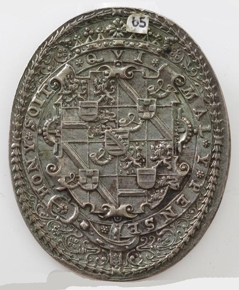Adv. Portrett, brystbilde med tekst omkring Rev. Hans kronede våpenskjold i rikt forsiret ramme. Tekst omkring.