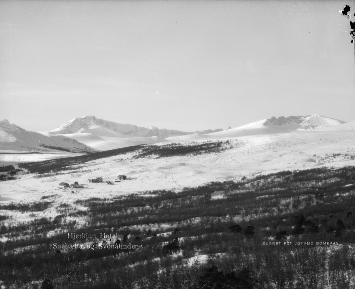 Oversikrsbilde med Hjerkinn fjellstue og bak fra høyre Snøhetta og Svånåtindan. Vinter. Påskrift: Hjerkinn hotel, Snehætta og Svonåtindene