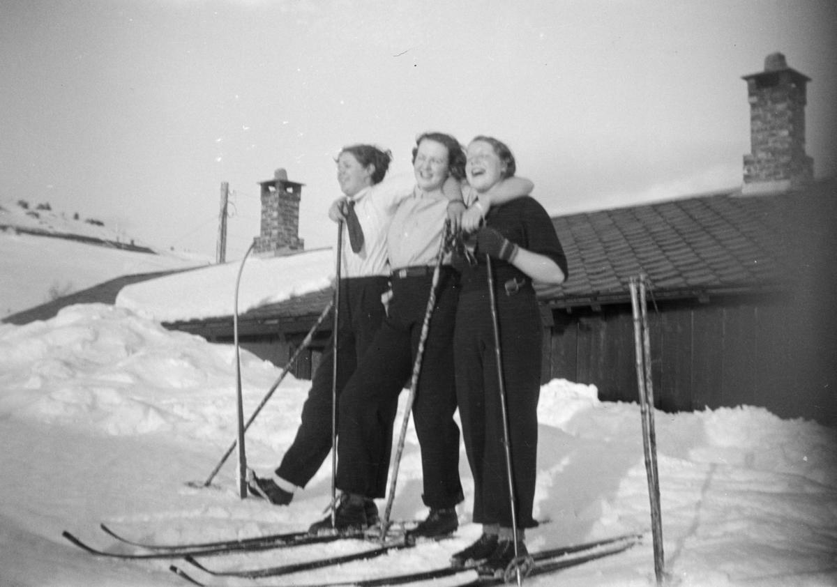 Tre kvinner på ski fremfor en hytte