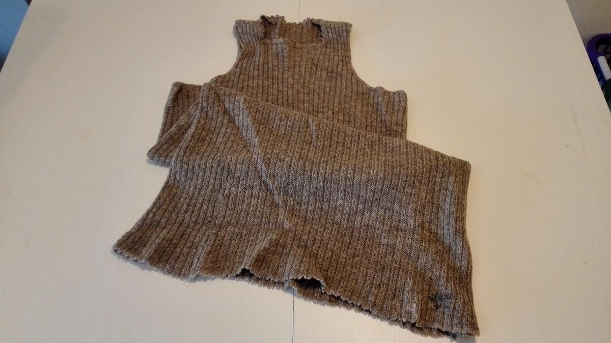 Underkjole samansett av 4 rektangulære stykke: framstykke, bakstykke og 2 sidestykke. Heile kjolen er ribbestrikka, men frå livet og ned er det strikka patentstrikk, der kast og lausmaske (1.omg.) er samanstrikka til vekselvis rett og vridd rett maske (2.omg.) og gjev buktande effekt (i kanten på ribbene). Den firkanta halsringningen er kanta med hekla tunger; ermringningane med fastmaskar. Frå buet etter strandsitjarplassen Henjesand,Hermansverk.