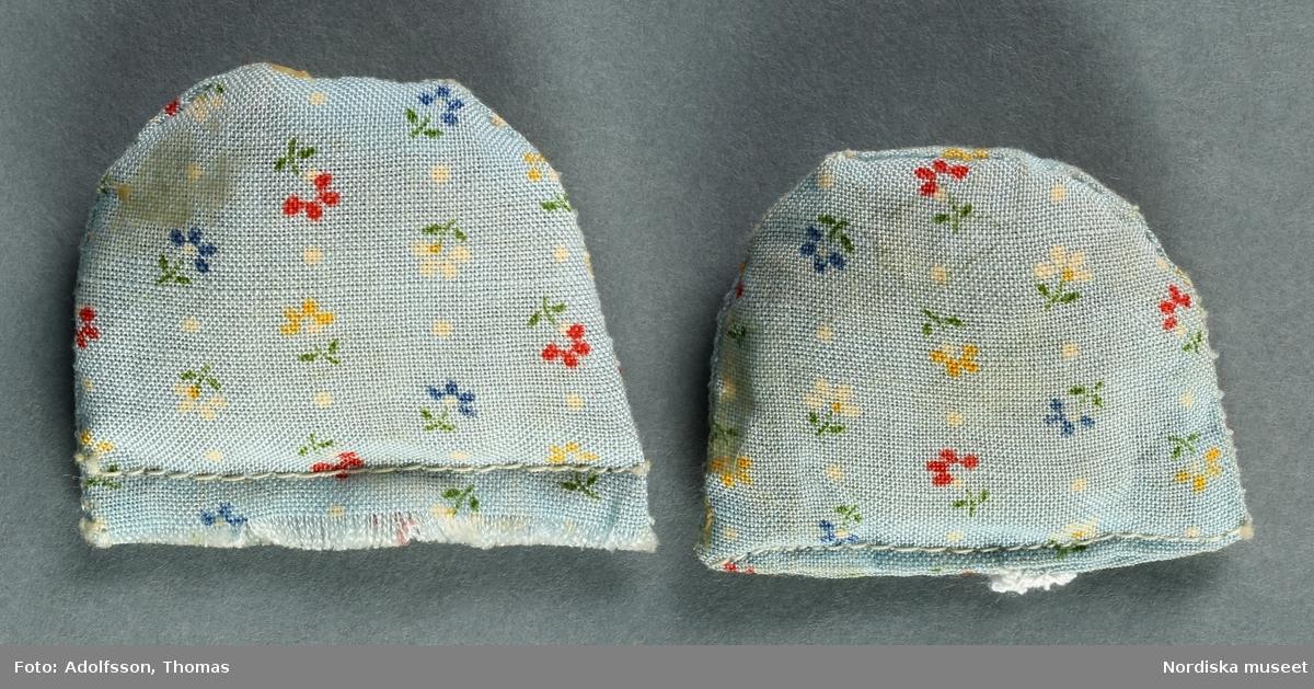 a) Vit dubbelsäng med gulddekor i bondrokokostil, trä och masonit, b) madrass av grönt bomullstyg, c) täcke av prickigt rosa syntet med spets samt d-e) två blommiga kuddar. Hör till inredningen i föräldrarnas sängkammare på andra våningen i dockskåpet.