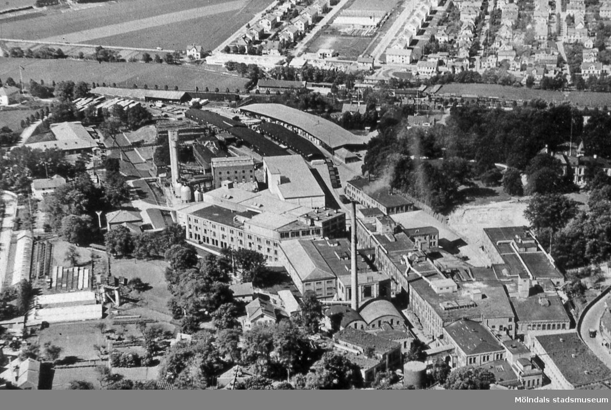Vy över pappersbruket Papyrus fabriksområde i Forsåker, Mölndal, år 1947. I bakgrunden ses bostadsbebyggelse i Åbyområdet och på Broslätt. Lägg även märke till Klings växthus mellan Prytzgatan och Åbybergsgatan. AF 10:3.