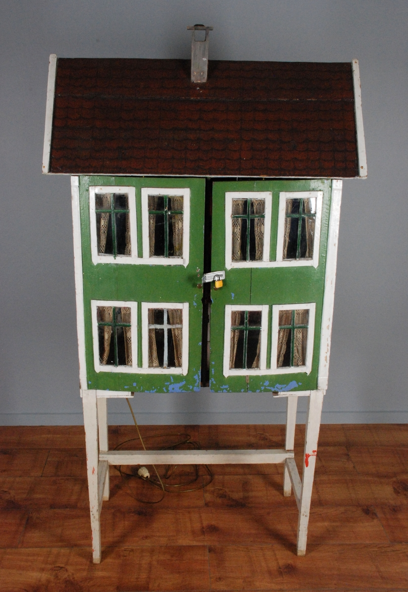Hus i 2 etasjer med saltak og skorsten. Ornamemtering i mønet på begge sider. 4 t-post vinduer i hver kortside, 8 i front. Baksiden er uten vinduer. Veggen på fremsiden er laget som en heldekkende tofløyet dør med beslag og hengelås på midten. Under beslaget er det en metallknott på hver dør. På baksiden er det festetlampettledninger som er ført gjennom veggen til hvert av lampepunktene i huset. Innvendig er huset delt i 2 etasjer med to rom i hver etasje. Kjøkken og soverom nede, to stuer oppe. Noen av rommene har fast inventar. Taket er dekormalt utvendig i taksteinsmønster. Huset står fastmontert på et stativ.