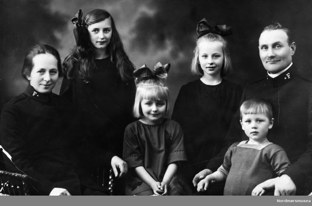Familiefoto på postkort., hvor foreldrene er i ført Frelsesarmeens uniform. Muligens fra Kristiansund. Fotograf er ukjent. Fra Nordmøre museums fotosamlinger.
