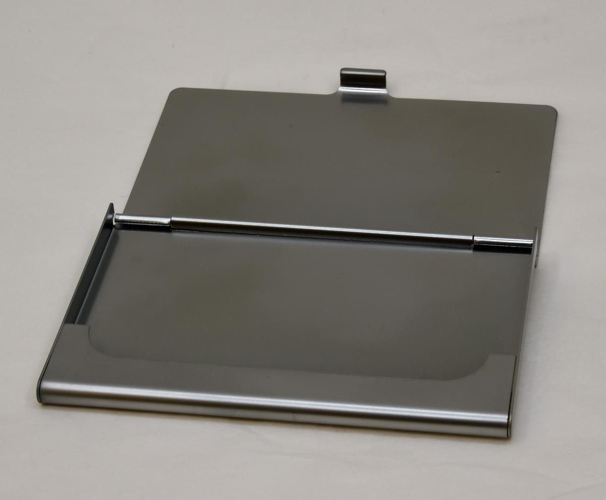 Korthållare av aluminium. Korthållaren är kvadratisk och har ett lock med tryckt text. Hållarens undersida har en uppvikt flik som formar en behållare för korten.(:1) Korthållaren ligger i en förpackning av papp.(:2)
