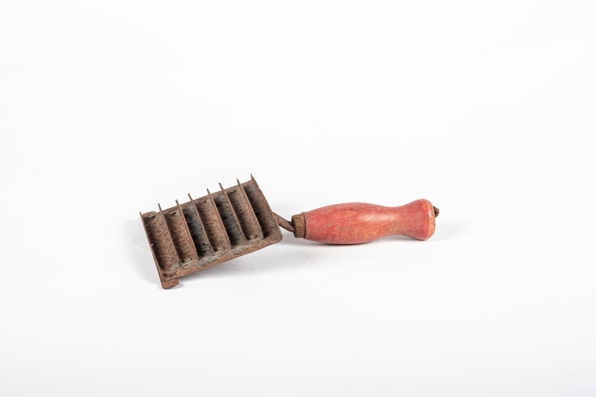 Strigle til hest som består av skrape av jern og dreid treskaft. Skrapen består av en plate med skrapekant i hver ende. På platen mellom skrapekantene er det tre tverrliggene skraper.