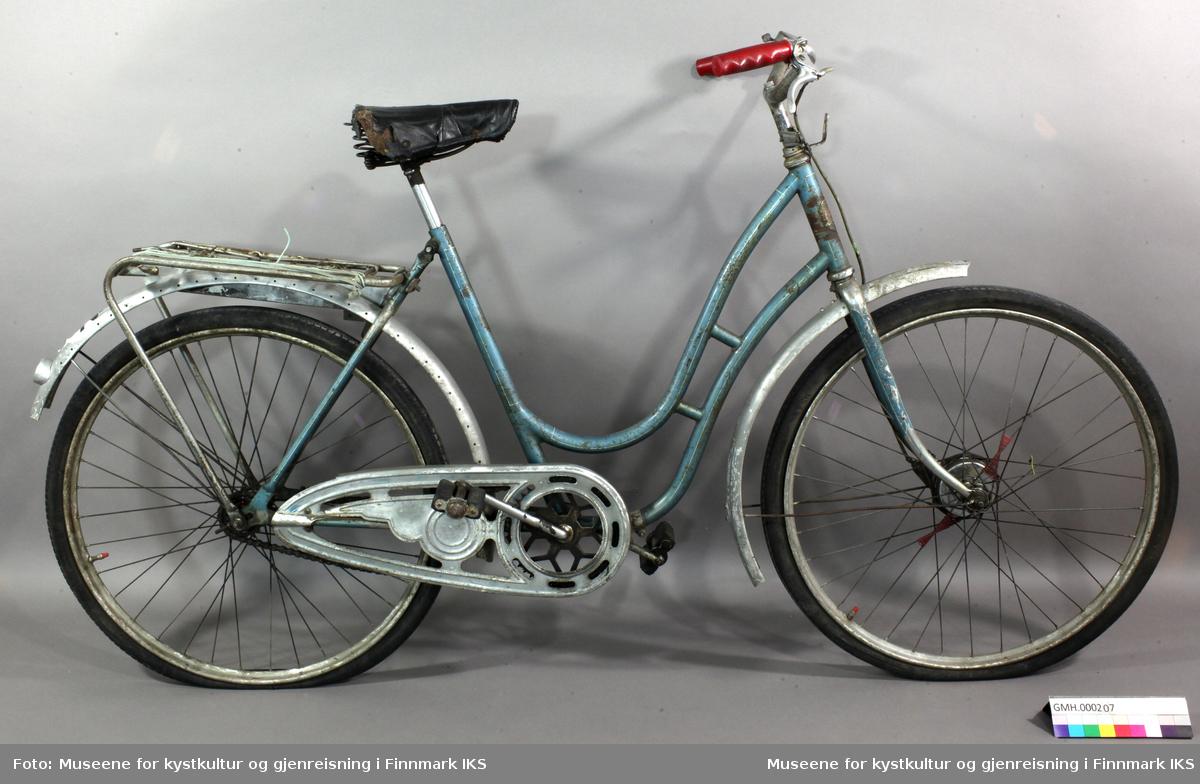 """Denne blåe damesykkelen med hvite streker har et svart, skinnliknende sete med merket """"LYCETT"""" bakpå, som er skrudd fast. Blåfargen går igjen på forskjermen i form av to blåe streker på hver side. Sykkelen har et sølvfarget bagasjebrett og like under er det festet en avlang boks i aluminium som har vært brukt til å oppbevare verktøy i. På bakskjermen er det en rund refleksbrikke innfelt. På styret er det ei bjelle/ringeklokke på venstre side og en bremsespake på høyre side. Under styret er det et feste for lykt. Sykkelstyret er kledd med røde plasthåndtak."""