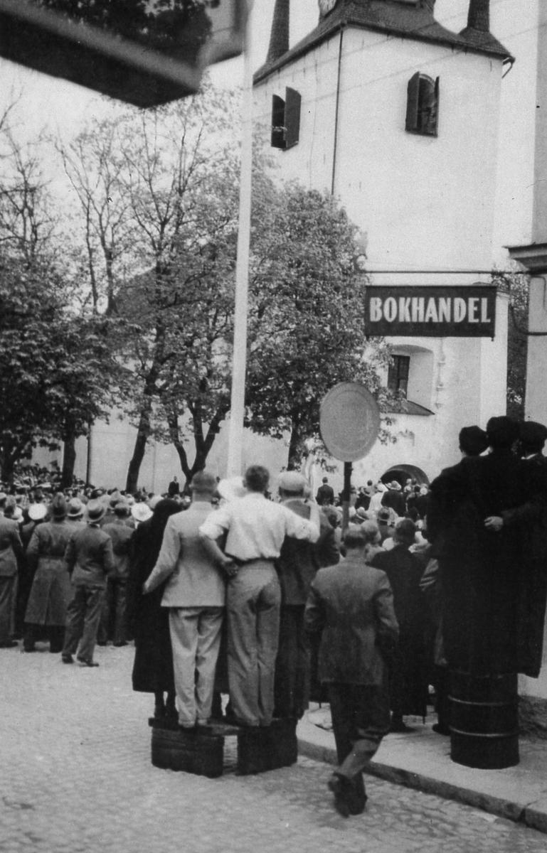 Mycket publik på Järntorget i samband med avtäckandet av Engelbrektstatyn. Detta är ett inslag i jubileumfirandet av Sveriges Riksdag. I förgrunden ses skylten till bokhandeln och i bakgrunden ses Heliga Trefaldighetskyrkan.