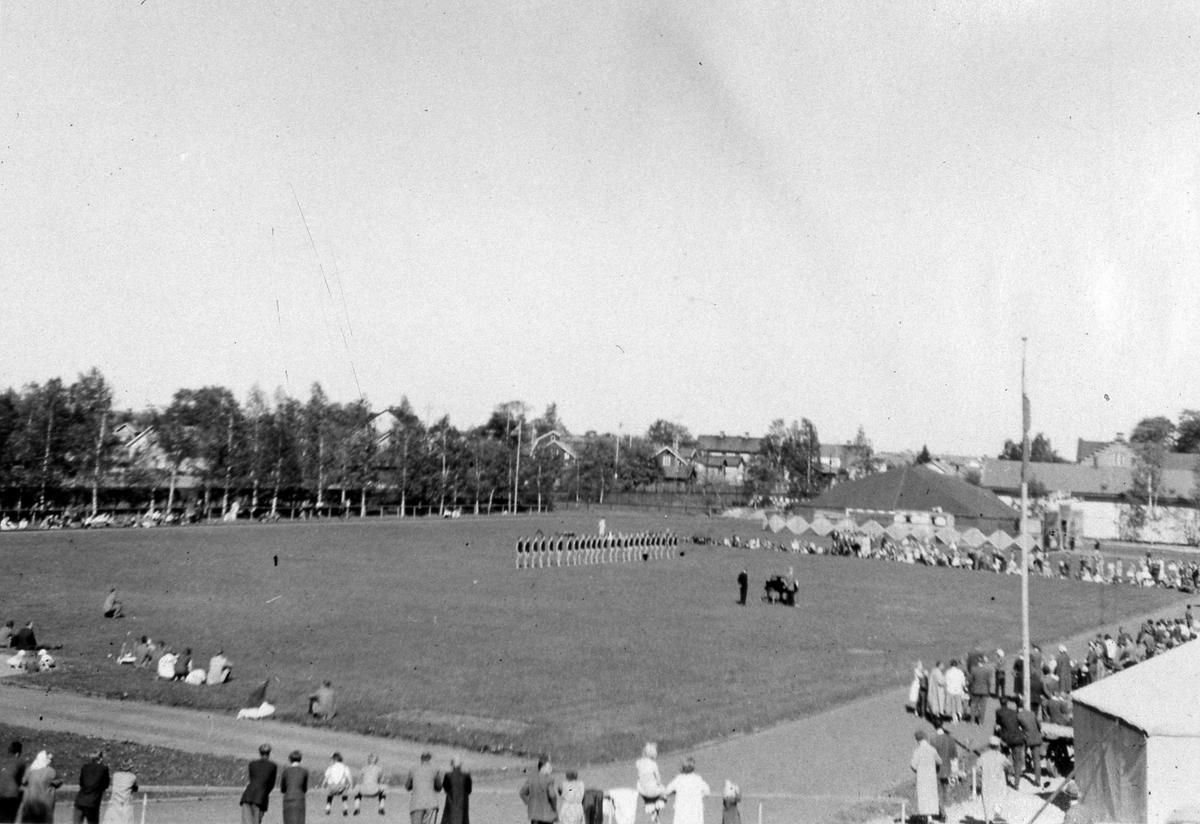 Gymnastikuppvisning på Sturevallen under Arbogautställningen. En grupp kvinnliga gymnaster står i rad på idrottsplanen. Bortanför dem ses ett tält. I bakgrunden ses bebyggelsen, till höger skymtar Arboga Margarinfabrik.