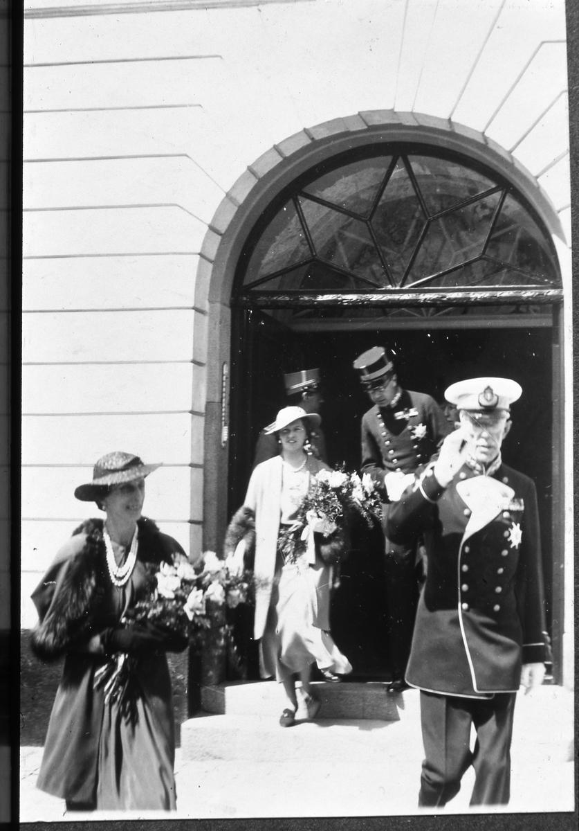 Stora delar av den kungliga familjen är i Arboga med anledning av firandet av Sveriges Riksdags 500-årsjubileum. Kungligheterna har gjort ett kort besök i Rådhuset. Från vänster; kronprinsessan Louise med svärfar kung Gustaf V. Bakom dem kommer prinsessan Sibylla med sin svärfar; kronprins Gustaf Adolf. Båda kvinnorna bär hatt och var sin stor blomsterbukett.
