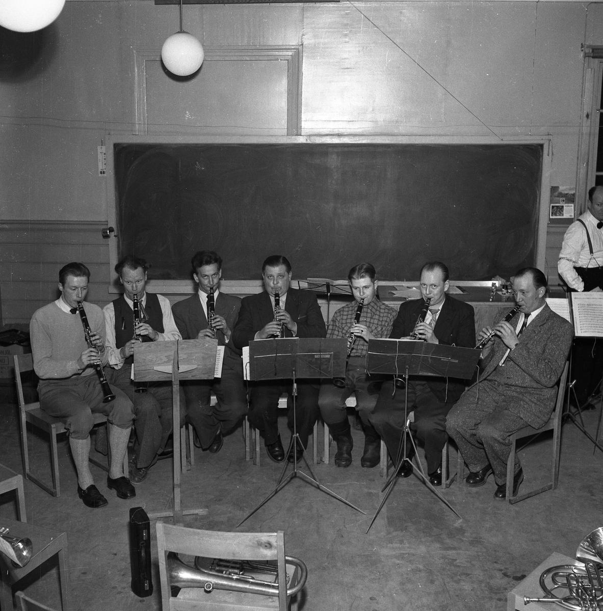 Klarinettisterna i Arboga Blåsorkester repeterar. Till höger i bild skymtar Herman Fält, dirigent.  Sju herrar spelar klarinett. Notställ.